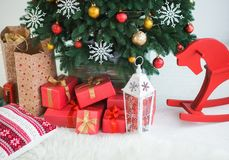 Many boxes wrapped in red festive paper under branches of pine Royalty Free Stock Photography
