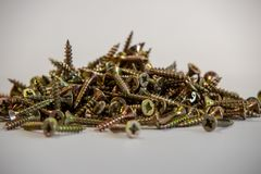 Many brass colored wood screws royalty free stock photo