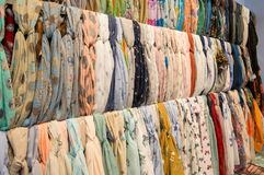 Many bright female scarfs and shawl. colorful scarves hanging in the market. clothes rack with a selection of scarves or scarfs. Pattern of many scarves stock photos