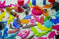 Many bright multi-colored objects printed on 3d printer lie on flat surface. Close-up. Fused deposition modeling, FDM. Concept modern progressive additive royalty free stock photo