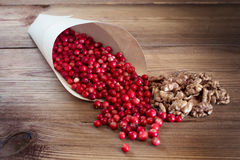 Many bright red cowberries and walnuts in a paper Royalty Free Stock Photos