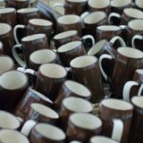Many brown coffee mugs in a line for sale Royalty Free Stock Photo