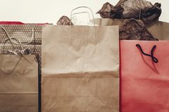 Many brown paper bags with presents on background of white wall. Royalty Free Stock Image