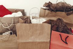 Many brown paper bags with presents on background of white wall. Royalty Free Stock Photos