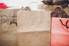 Many brown paper bags with presents on background of white wall. Stock Photos