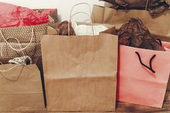 Many brown paper bags with presents on background of white wall. Stock Photo