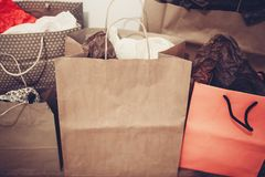 Many brown paper bags with presents on background of white wall. Royalty Free Stock Photo