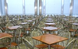 Many brown square eating tables and metal chairs staying in empty cafe hall Royalty Free Stock Image