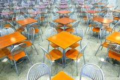 Many brown square eating tables and metal chairs staying in empty cafe hall Stock Photo