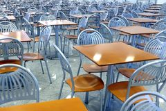 Many brown square eating tables and metal chairs staying in empty cafe hall Royalty Free Stock Photo