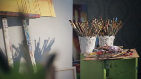 Many brushes artist. Palette with paint near the painting on the easel. light from the window stock footage