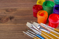 Many brushes and paint pots on wooden table background Royalty Free Stock Image