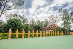 Many Buddha statues in perspective at the buddhist temple Royalty Free Stock Image