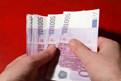 Many bundle of 500 Euro bank notes in man's hands. Close-up of many bundle of 500 Euro bank notes in man's hands, red leather, consider stock photos