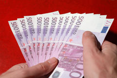 Many bundle of 500 Euro bank notes in man's hands. Close-up of many bundle of 500 Euro bank notes in man's hands, red leather stock images