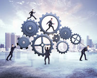 Many businessman pushing gears Stock Images