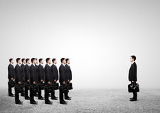 Many businessmen with briefcase. Concept of many businessmen with briefcase against one stock image