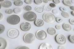 Many buttons assorted on white background. Many clothing buttons on white background Stock Photos