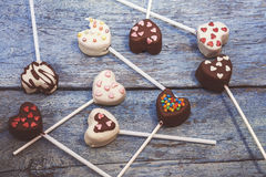 Many Cake Pops in the form heart lie on the old blue wooden back. Ground top view royalty free stock photo