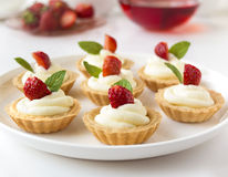 Many cakes, cupcakes with fresh fruits (strawberries), whipped cream, jelly and mints Stock Photo