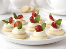 Many cakes, cupcakes with fresh fruits (strawberries), whipped cream, jelly and mints Royalty Free Stock Photo