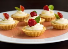 Many cakes, cupcakes with fresh fruits (strawberries), whipped cream, jelly and mints Stock Photos