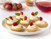 Many cakes or mini tart with fresh fruits, whipped cream and mints royalty free stock photography