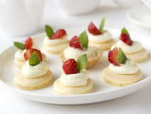 Many cakes or mini tart with fresh fruits, whipped cream and mints Stock Image