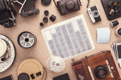 Many cameras roll of films, contacts on wooden cork table. Photographer workspace. Flat lay. View from above. Stock Images