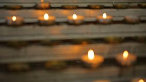 Many candle flames glowing in the dark, create a spiritual atmosphere.  stock video