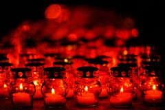 Many candles burning in red candle holders at night Royalty Free Stock Image
