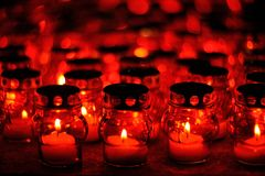 Many candles burning in red candle holders at night Stock Image