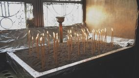 Many candles. Many candles glowing on table in the church stock footage