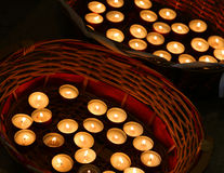 Many candles lit in the wicker basket Royalty Free Stock Photo