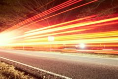 Many cars are driving at night on a highway and create light trails royalty free stock photo