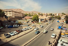Many cars driving on small iranian city. KURDISTAN, IRAN: Many cars driving on small iranian city under blue sky in Middle East. Islamic Republic of Iran is the Royalty Free Stock Photography