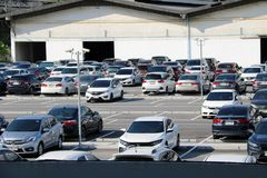 Many cars are parked at the outdoor parking lot and garage building. stock image