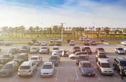 Many cars are parked at outdoor parking lot, people walk. royalty free stock photo