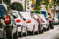 Many Cars Parked On Street In City In Sunny Summer Day. Row Of City Cars. Many Cars Parked On Street In European City In Sunny Summer Day.  Row Of City Cars Royalty Free Stock Image