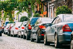 Many Cars Parked On Street In City In Sunny Summer Day. Row Of City Cars. Many Cars Parked On Street In European City In Sunny Summer Day.  Row Of City Cars Stock Photo