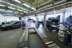 Many cars stand in car garage with special equipment Royalty Free Stock Images