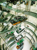 Many cars suspended on a steel cable in the car sales center. The construction of cars in the center of the auto store. Royalty Free Stock Images
