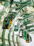 Many cars suspended on a steel cable in the car sales center. The construction of cars in the center of the auto store. Stock Photo