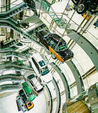 Many cars suspended on a steel cable in the car sales center. The construction of cars in the center of the auto store. Stock Images