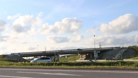Many cars, trucks move on road and under overpass. At summer day stock video footage
