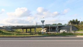 Many cars, trucks move on road and under overpass at sunny day. Time lapse stock footage