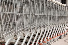 Row of metal shopping carts. Many carts one behind the other outside a mall Royalty Free Stock Photos