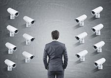 Many CCTV cameras on one wall, rear view of a man. Fourteen CCTV cameras hanging in rows on one concrete wall facing a businessman looking at the wall. Concept stock image