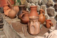 Many ceramic handmade utensils on stone shelf outdoor. royalty free stock photo