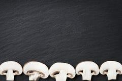 Many champignons framing dark stone copyspace. Royalty Free Stock Images